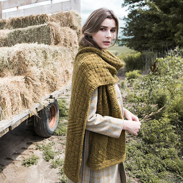 Oversized knitted scarf in basketweave, diamonds, and diagonal patterns in tiger's eye colored yarn.