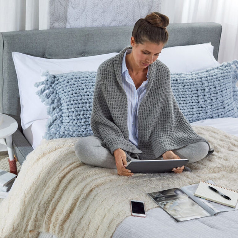 Women Wearing Red safe haven shawl, siting on a bed and looking at her iPad