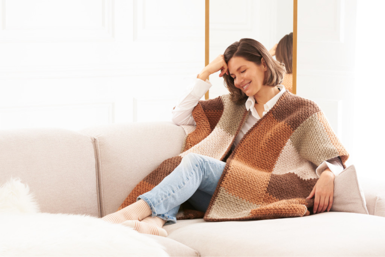 Women Wearing Caron Crochet Colorblock Ruana, Siting on Sofa with a smile on her face