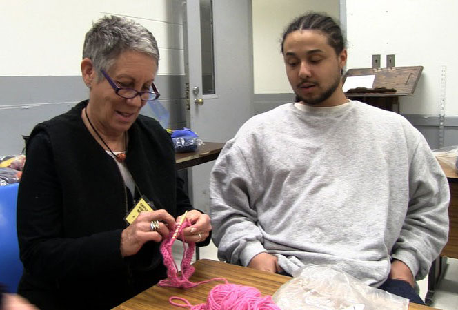 Lynn teaching inmate to knit