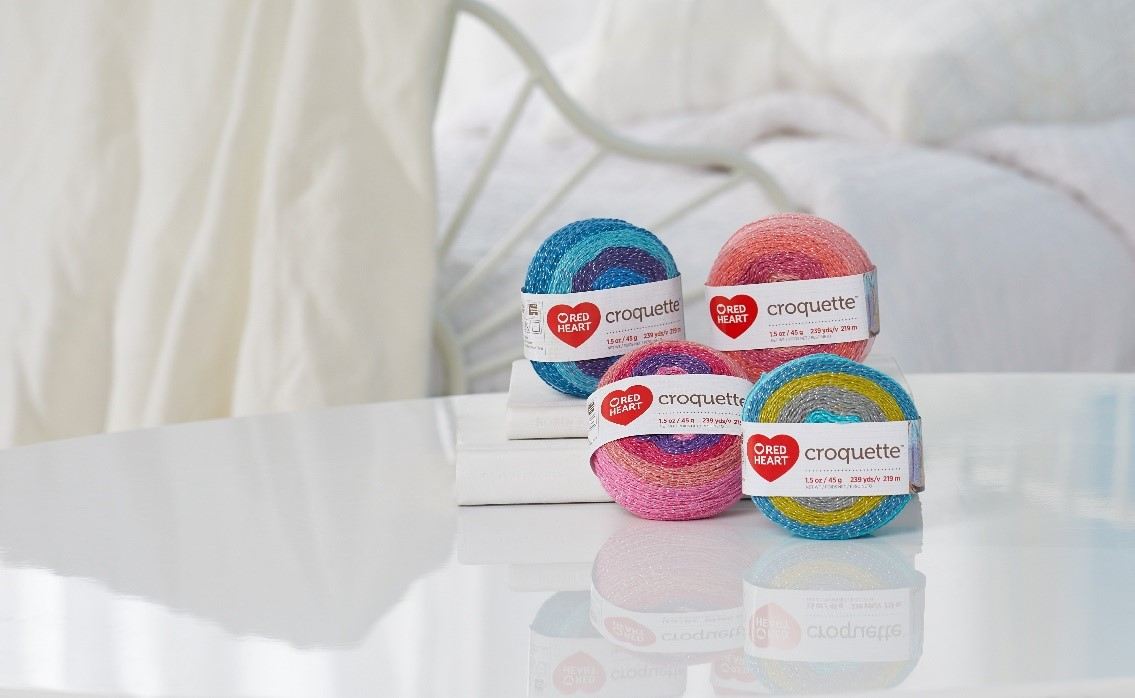 Four Red Heart Croquette yarn is placed on the table top in different colors.