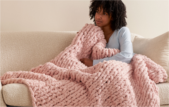 Women siting on sofa and the blanket in hand