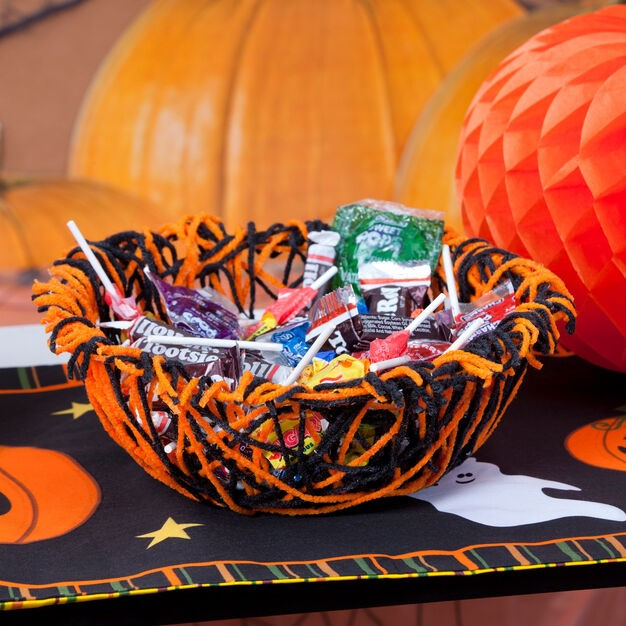 A basket of candy for the halloween treat is placed on the table