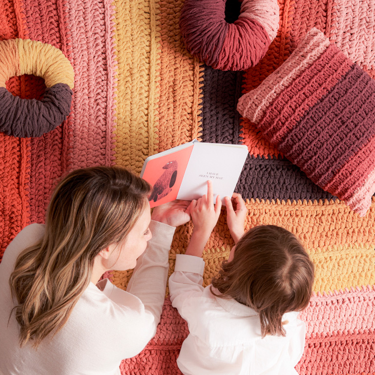 Mom and daughter reading a book on a blanket